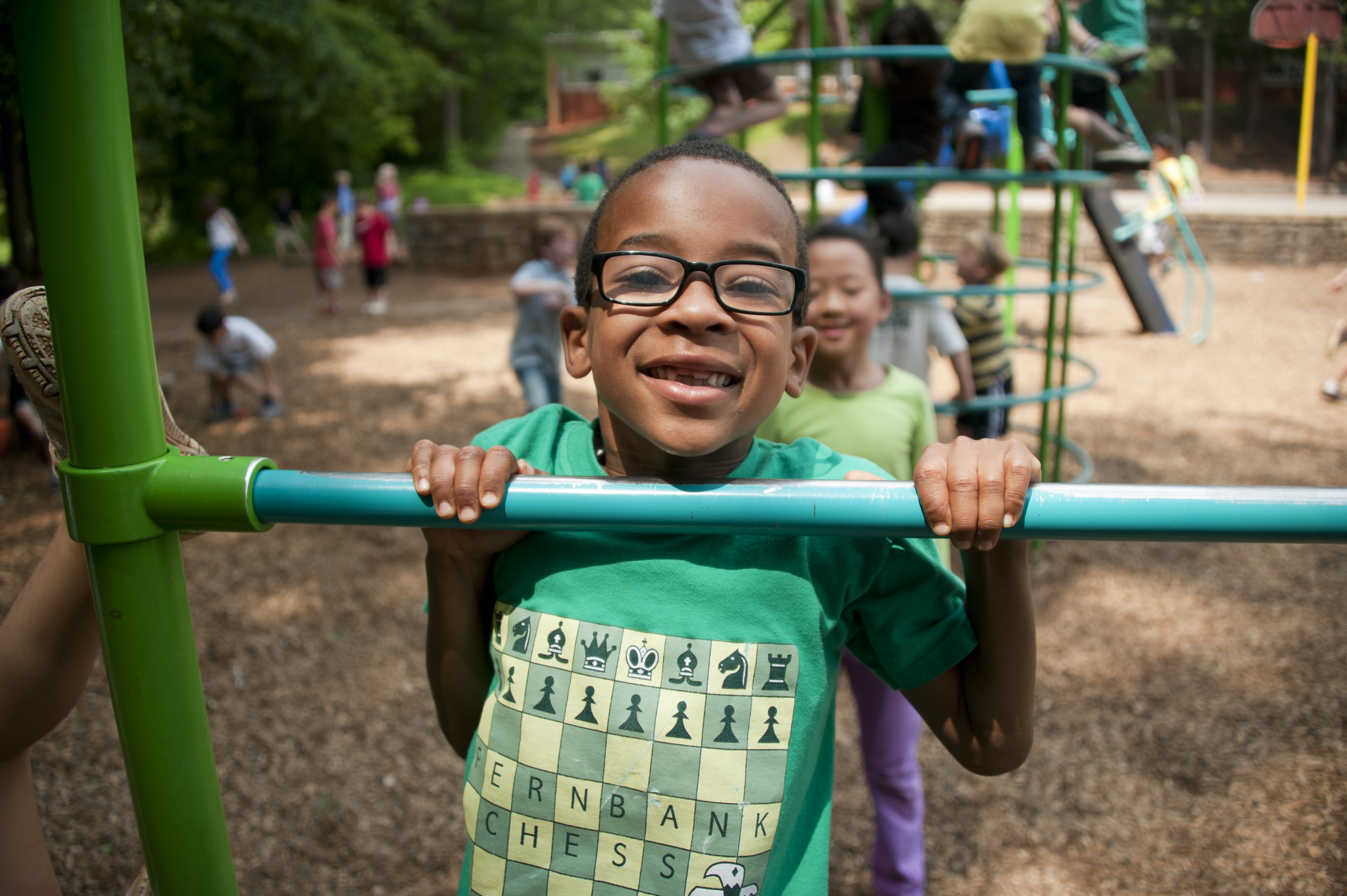 Decorative Image of a boy in a green t-shirt wearing glasses plays on a metal playground equipment.