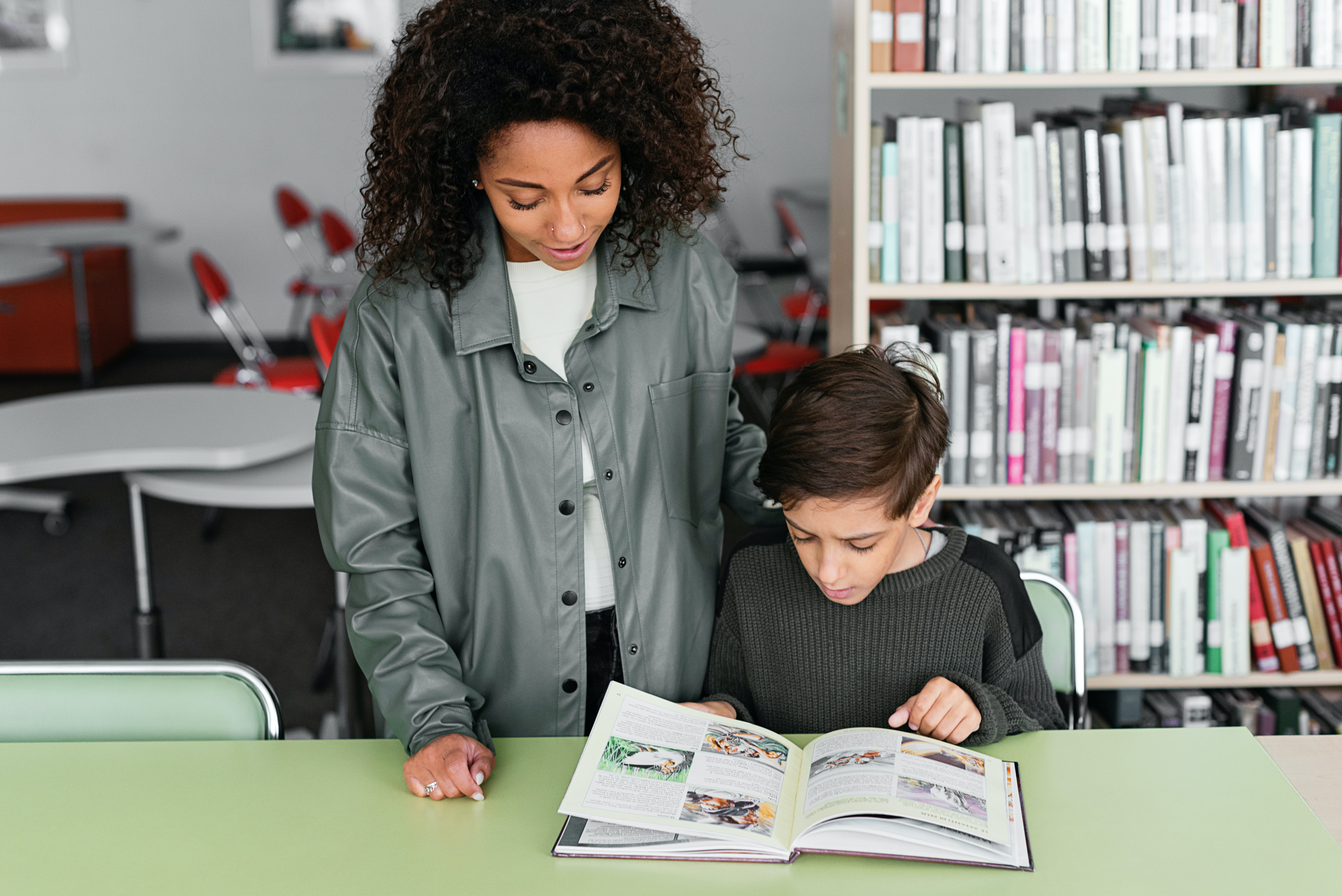 Two kids are at a light green table in a library. One kid is standing and appears to be an older black female in a green jacket and white shirt. The second kid is sitting and appears to be a younger male learning to read.